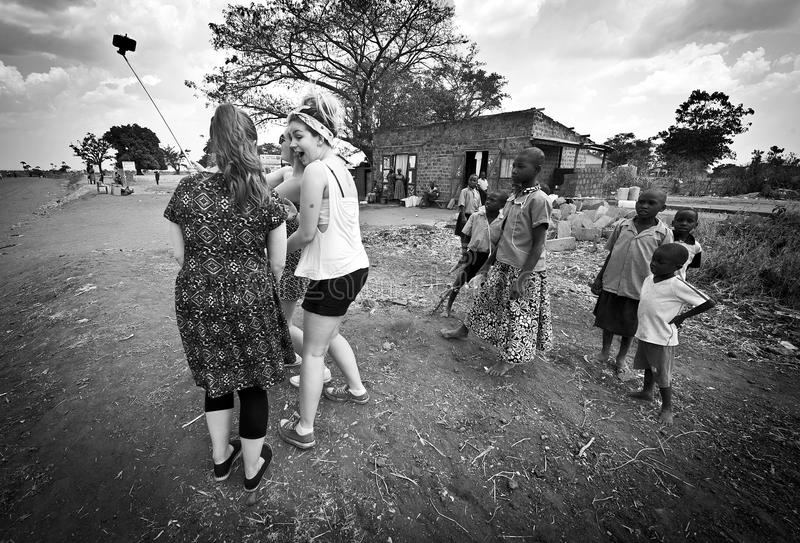 De westelijke tieners ontmoeten Afrikaanse kinderen stock fotografie