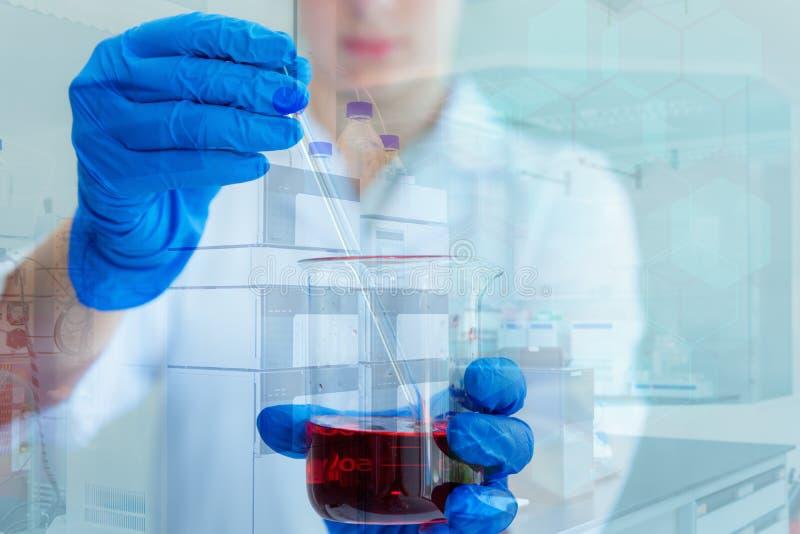 De wetenschappelijk onderzoeker beweegt en mengt vloeibaar chemisch product in beker stock afbeelding