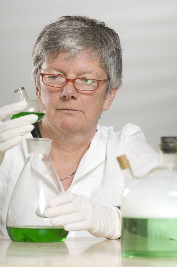 De wetenschapper werkt met een groene vloeistof royalty-vrije stock foto