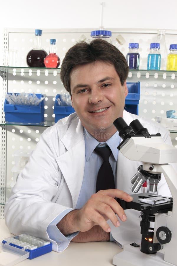 De wetenschapperzitting van de onderzoeker bij laboratoriumbureau stock foto's