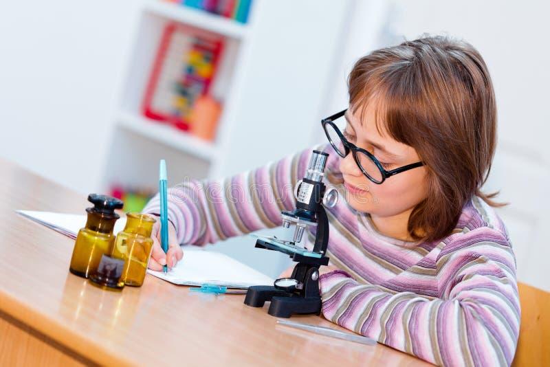 De wetenschapsmeisje van de tiener met microscoop royalty-vrije stock fotografie