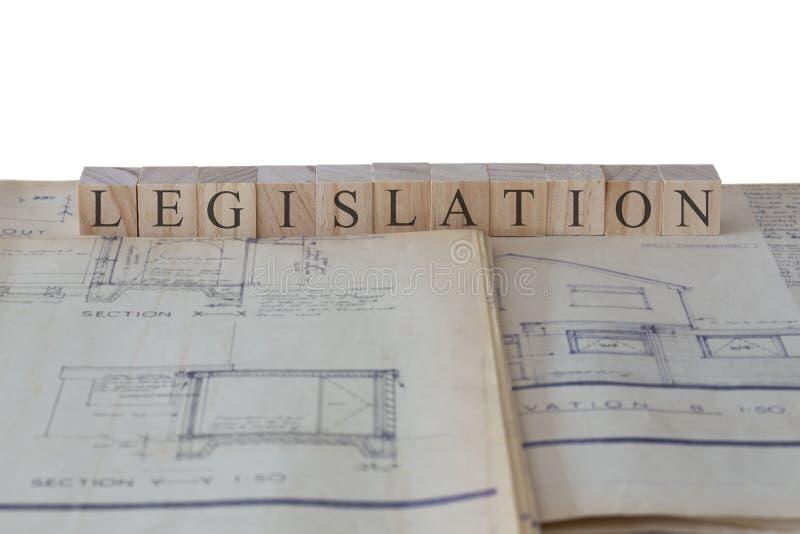 De wetgeving op houten blokken op de bouwtekeningenblauwdrukken die van de huisuitbreiding wordt geschreven royalty-vrije stock foto's