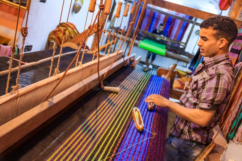 De wever werkt aan textiel op een weefgetouw in een opslag in Fes-medina in M royalty-vrije stock fotografie