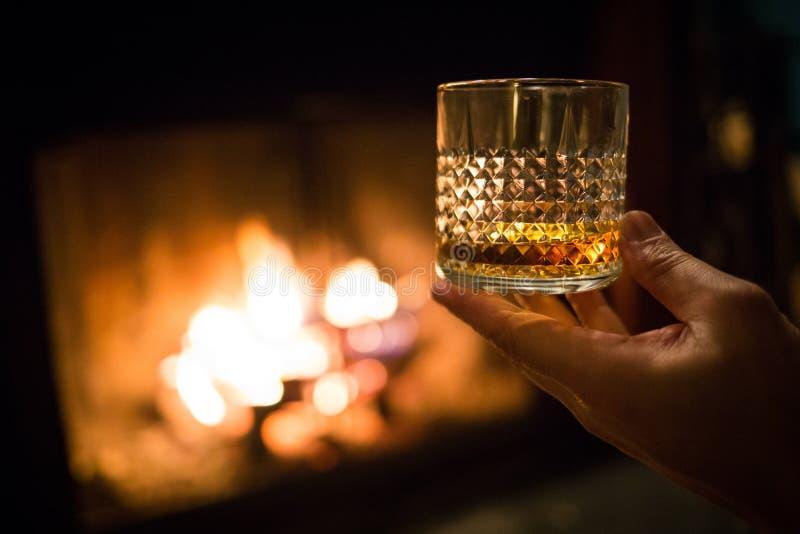 De whiskyglas van de handholding bij open haard stock afbeelding