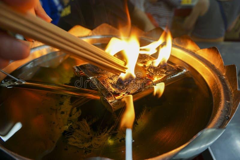 De wierook wordt aangestoken door brand Van een grote lamp stock fotografie
