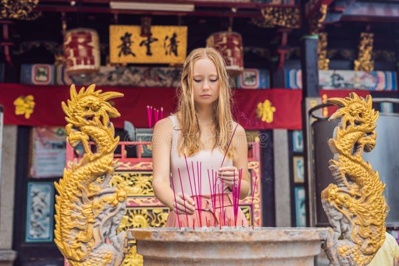 De wierookstokken op joss stokpot branden en roken gebruik voor loonseerbied aan Boedha, Wierookstokken in vrouwenhand royalty-vrije stock foto's