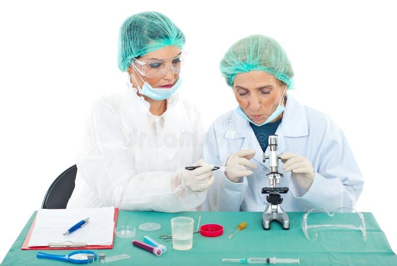 De wijfjes die van wetenschappers microscoop gebruiken stock afbeelding