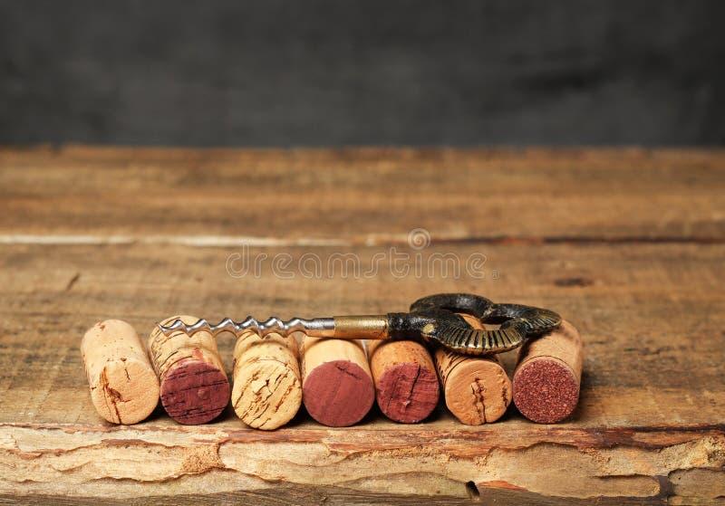 De wijn kurkt het liggen op een uitstekende houten lijst met kurketrekker royalty-vrije stock afbeelding