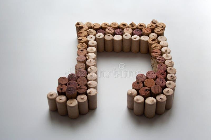 De wijn kurkt muzieknota over witte achtergrond stock fotografie