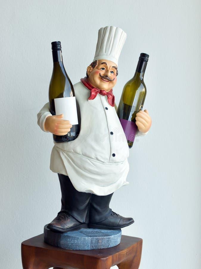 De wijn van de holdingsflessen van de chef-kokpop op witte achtergrond royalty-vrije stock foto