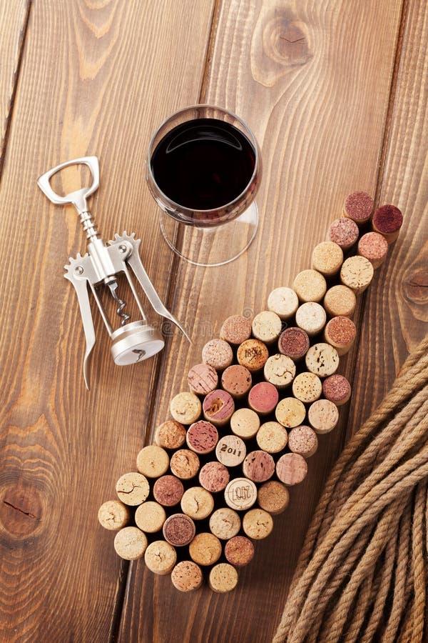 De wijnfles vormde kurkt, glas rode wijn en kurketrekker stock foto's