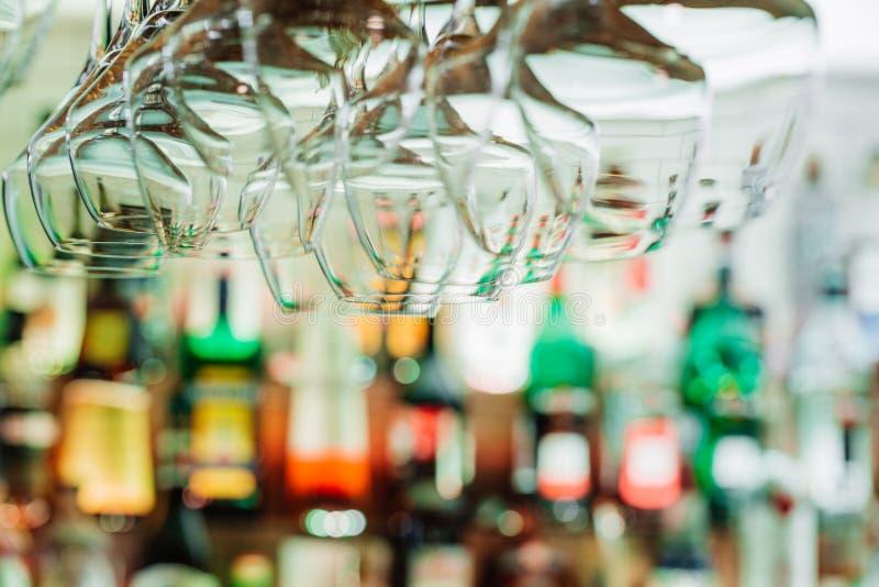 De wijnglazen die van metaalstralen hangen defocused achtergrond S stock afbeeldingen