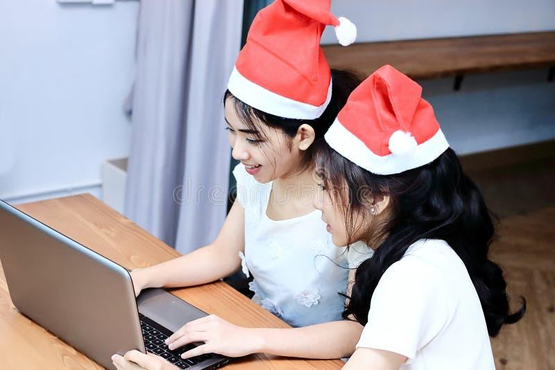 De wijnoogst stemde beeld van vrolijke jonge Aziatische vrouwen die in Kerstmanhoeden online met laptop in woonkamer thuis winkel royalty-vrije stock foto's