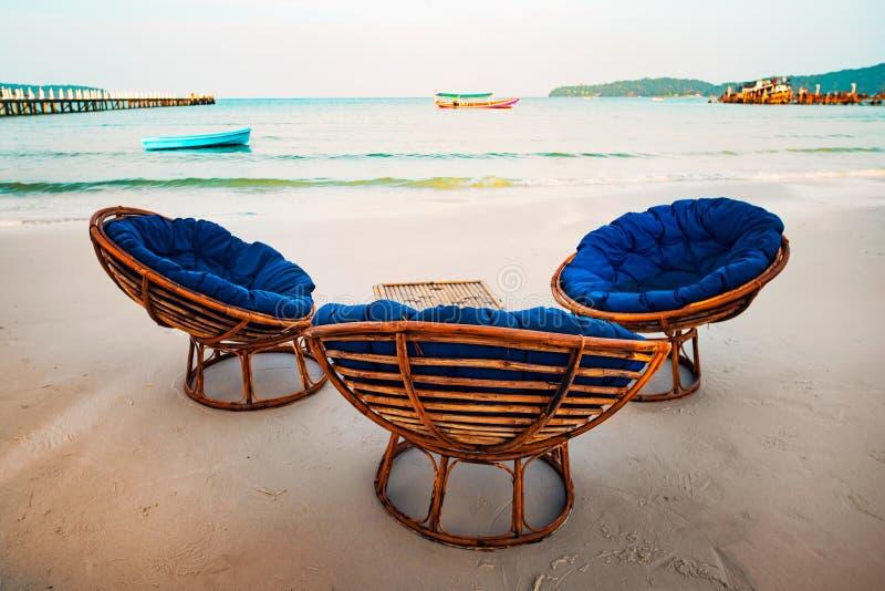 De wijnoogst stemde twee ligstoelen op tropische kust concept recreatie en toerisme op tropisch eiland zittingsstoelen op zand stock afbeelding