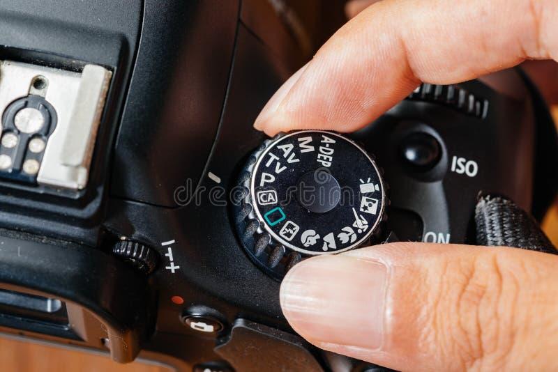De wijze van de programmawijzerplaat op dslrcamera met vingers op de wijzerplaat stock foto
