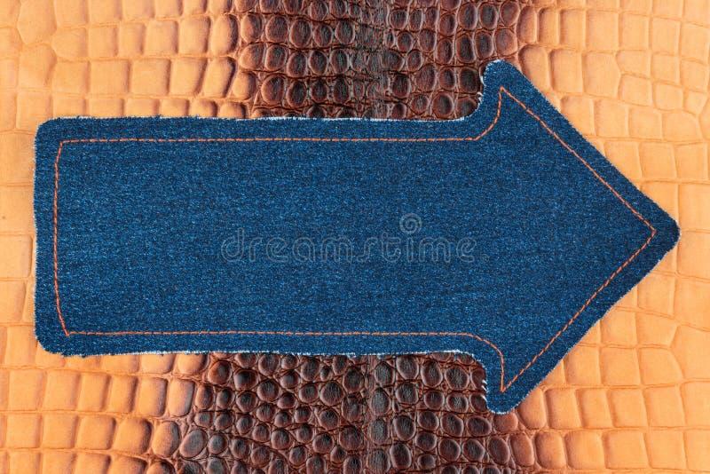 De wijzer van denim wordt gemaakt ligt op een bruine krokodilhuid, met ruimte voor uw tekst die royalty-vrije stock afbeeldingen