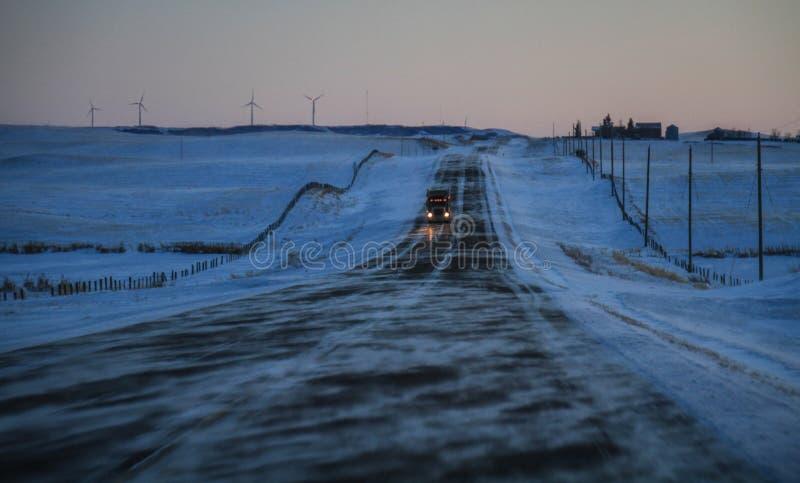 De wind blaast ijzige mist op de weg naar lethbridge bij schemer, Alberta, Canada stock fotografie