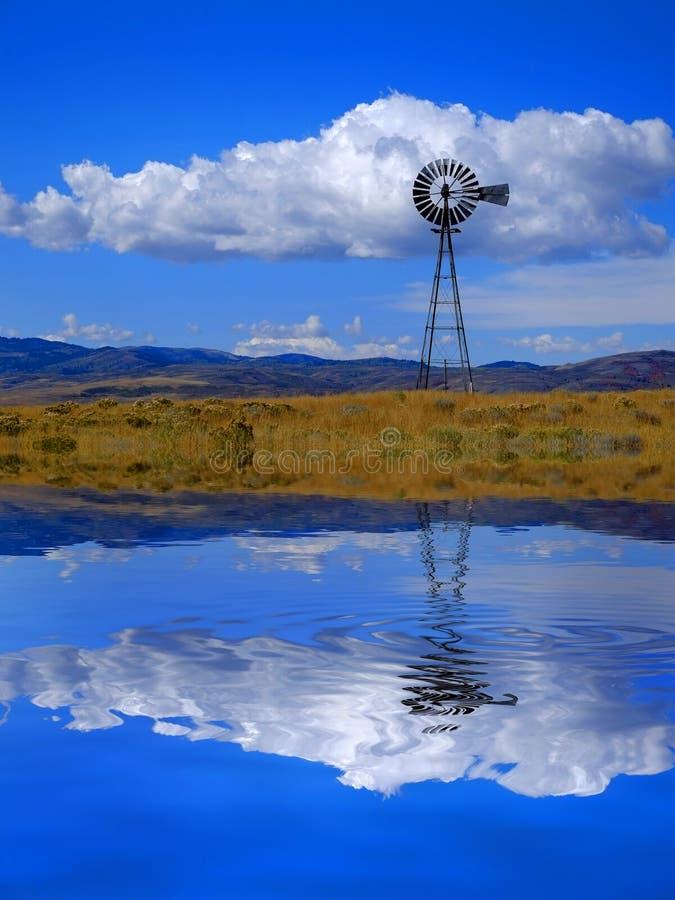 De windmolen op Helling in Platteland Landelijk Amerika met Hemel en de Wolkenbezinning in het Meer van de Watervijver denken na royalty-vrije stock fotografie