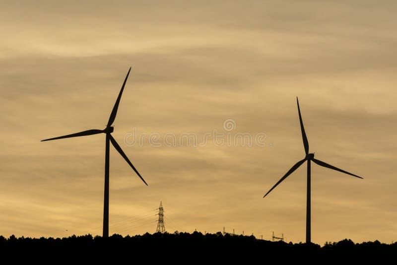 De windmolens produceren elektrisch voor onze wereld royalty-vrije stock afbeelding