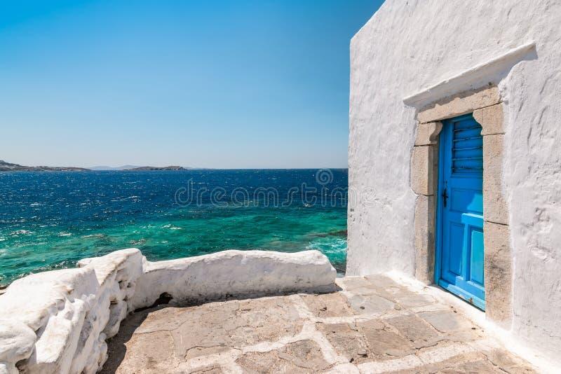 De windmolens van Mykonos - Griekenland De traditionele witte bouw met blauwe deur bij de kust royalty-vrije stock foto