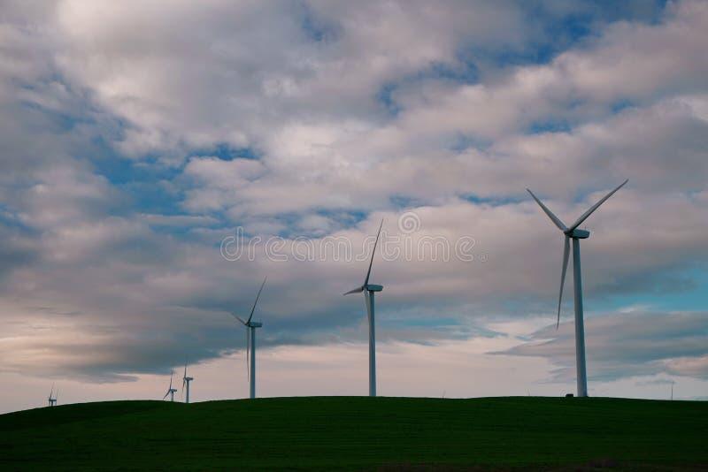 De windmolenturbines zijn close-up tegen de achtergrond van zonsondergangwolken royalty-vrije stock foto's