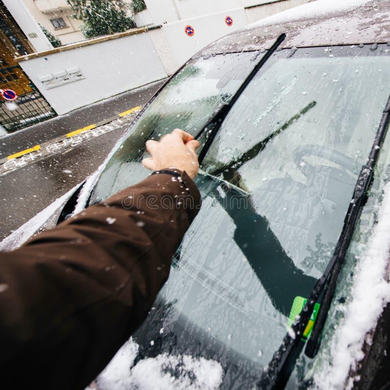De windschermenwissers van de mensen schoonmakende auto alvorens te drijven royalty-vrije stock afbeelding