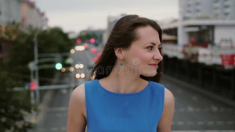 De windslagen snakken donkere haar mooie jonge vrouwen gelukkig, het glimlachen meisje de status op de brug en bekijkt de camera  stock fotografie
