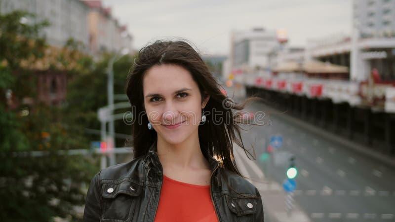 De windslagen snakken haar mooie jonge vrouwen gelukkig, het glimlachen meisje de status op de brug en bekijkt de camera 4K royalty-vrije stock foto's