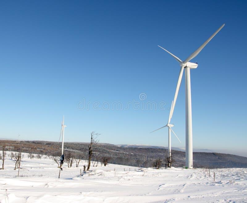 De windturbine van de elektriciteit in de winter stock foto's