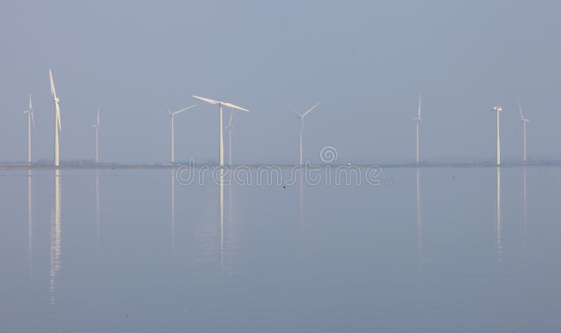 De windturbines en de blauwe die hemel in water van eemmeer worden weerspiegeld huizen dichtbij in Holland stock afbeelding