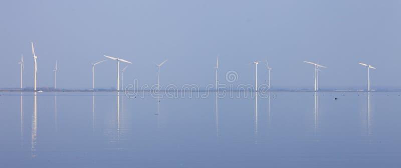 De windturbines en de blauwe die hemel in water van eemmeer worden weerspiegeld huizen dichtbij in Holland royalty-vrije stock foto's