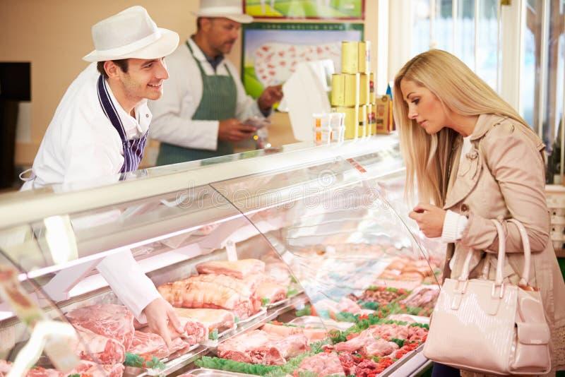 De Winkel van slagersserving customer in stock afbeeldingen