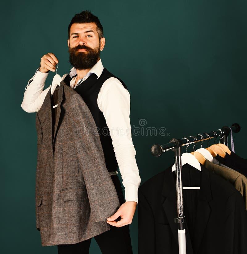 De de winkelmedewerker of verkoper stellen grijs kostuum op kleerhanger voor De zakenman met netelig gezicht probeert jasje op gr stock fotografie