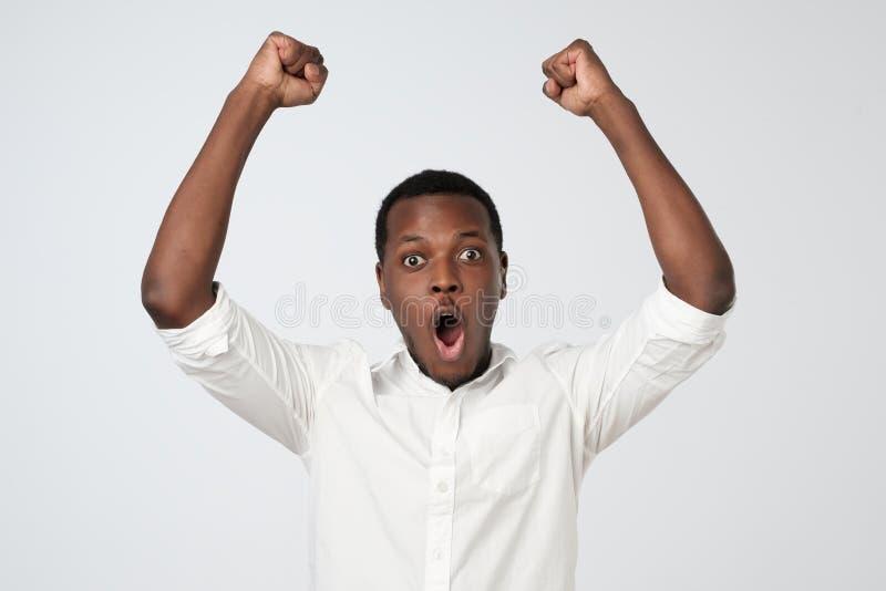 De winnaar viert Opgewekte Afrikaanse mens met de gelukkige omhoog vuisten van de gelaatsuitdrukkingholding stock afbeeldingen