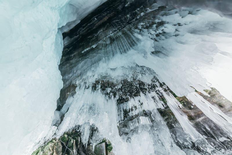 De winter Baikal Het eiland van Olkhon ijsgrot Dikke blauwe ijs en ijskegels op de kustrotsen van Olkhon-Eiland in de winter stock foto's