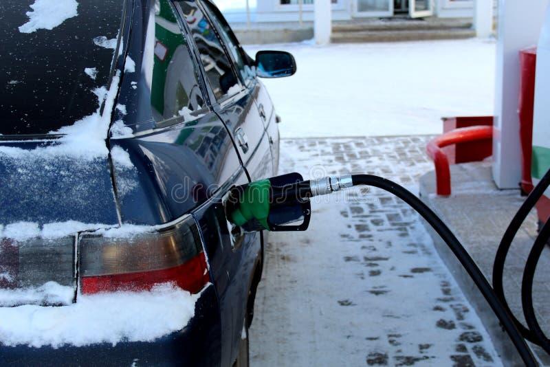 In de winter bij het benzinestation tank de auto bij stock afbeeldingen