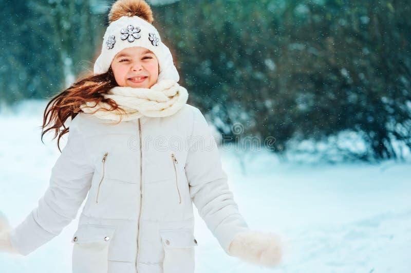 De winter dicht omhooggaand portret van leuk dromerig kindmeisje in witte laag, hoed en vuisthandschoenen stock foto's