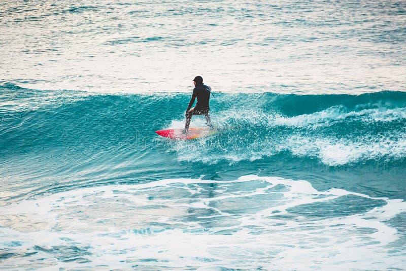De winter die in oceaan surfen Surfer op Blauwe Golf stock afbeeldingen