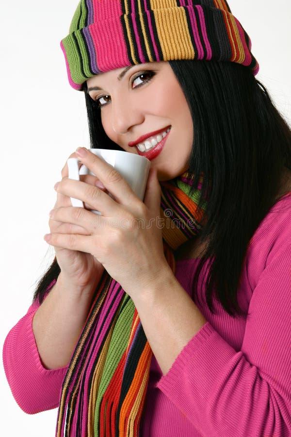 De winter gestileerde vrouw die een koffiemok houdt stock foto
