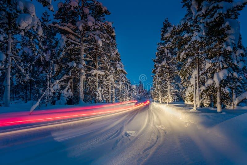 De winter het Drijven - Lichten van auto en de winterweg in bos bij nigh stock foto's