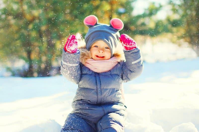 De winter het gelukkige het glimlachen kind spelen met sneeuw royalty-vrije stock fotografie