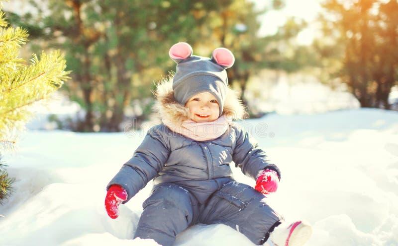De winter het gelukkige het glimlachen kind spelen in sneeuw bij zonnige dag stock foto's
