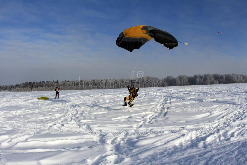De winter het skydiving Een yellowsuit skydiver landt op de sneeuw stock afbeelding