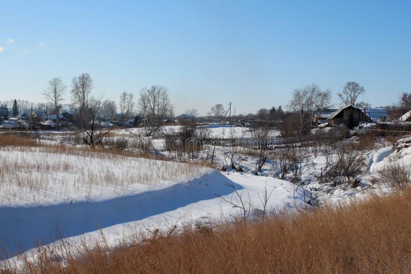 De winter landelijke landschap bevroren rivier een dorp op de helling van de kust op een duidelijke dag royalty-vrije stock afbeelding