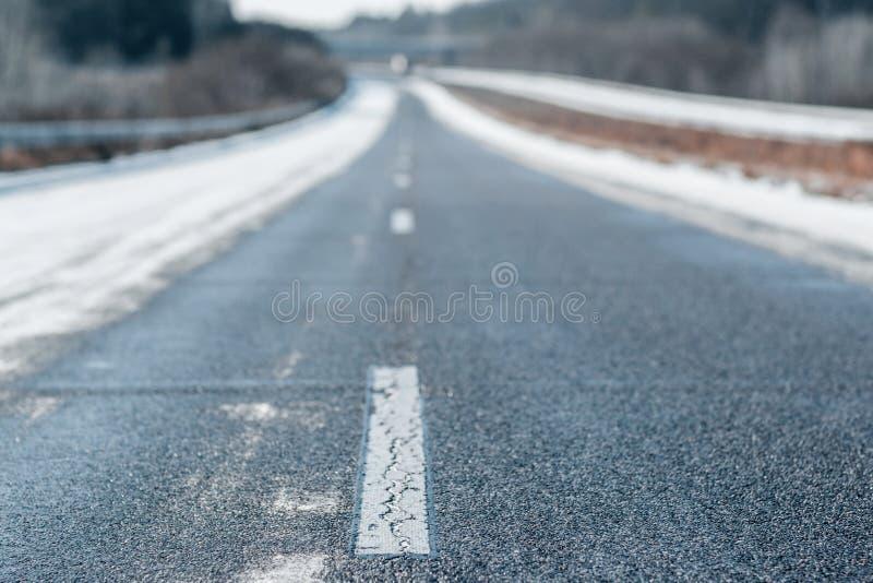 De winter lege weg met een gestormde witte lijn royalty-vrije stock fotografie