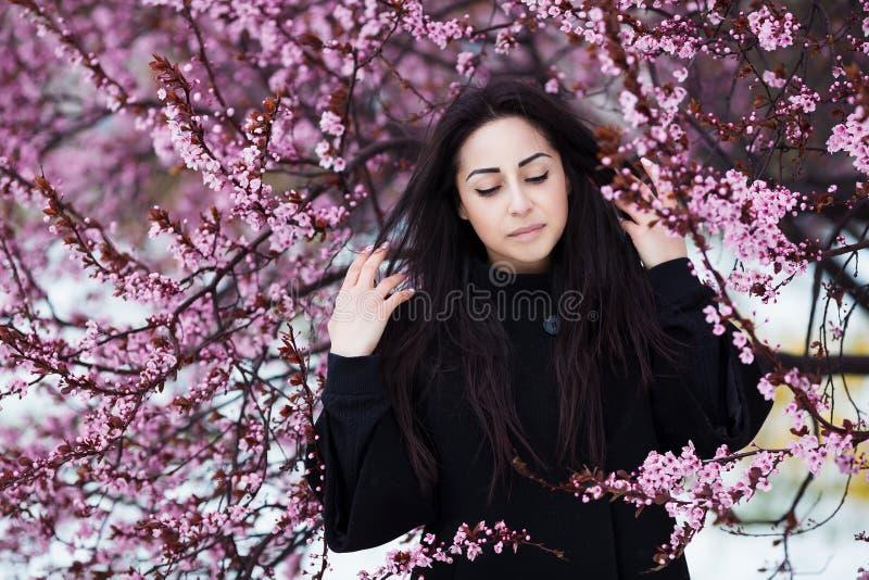 De winter, de lenteportret van jonge mooie donkerbruine vrouw die warme laag dragen Bloemen en de manierconcept van de sneeuwscho stock foto