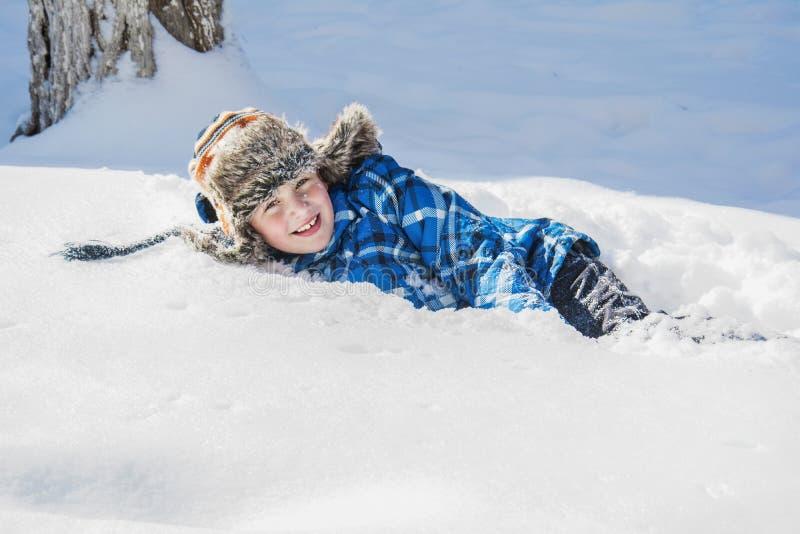 In de winter, ligt een gelukkige jongen op de sneeuw stock fotografie