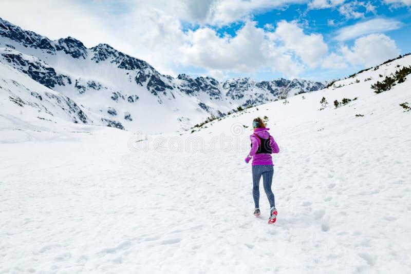 De winter lopende vrouw De inspiratie van de sleepagent, sport en fitnes stock foto