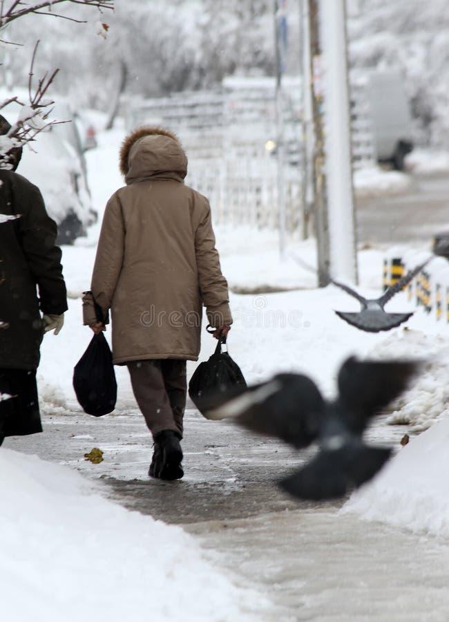 De winter De mensen lopen op een zeer sneeuwstoep Mensenstap op een sneeuw-verdwaalde weg Ijzige stoep Ijs op stoepen royalty-vrije stock foto