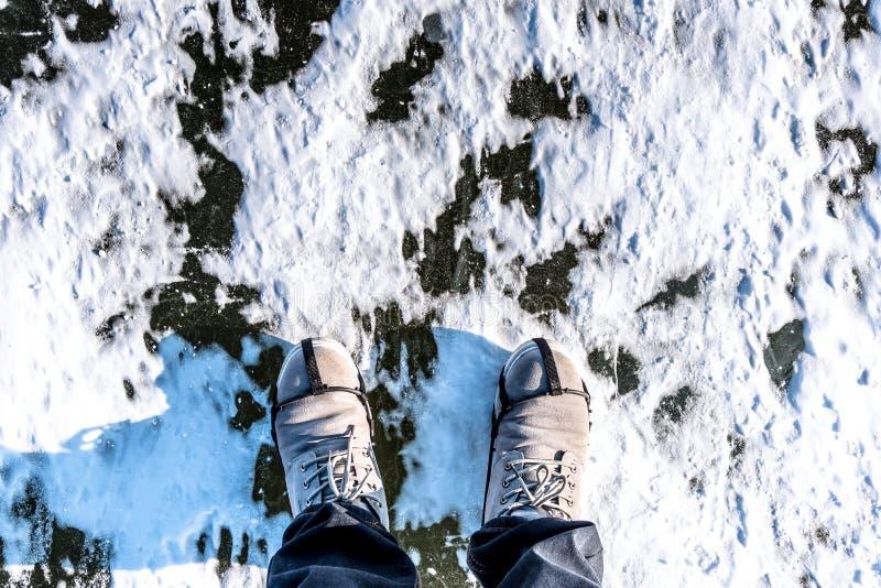 In de winter Mensenslijtage behandelden de wandelingslaarzen die zich op een bevroren ijs bevinden rive sneeuw stock foto's